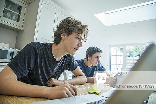 Two teenage boys using laptop and tablet on table at home
