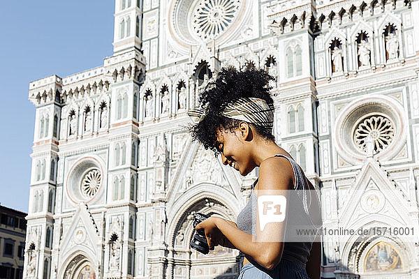 Lächelnde junge Frau schaut in die Kamera vor der Kathedrale  Florenz  Italien Lächelnde junge Frau schaut in die Kamera vor der Kathedrale, Florenz, Italien