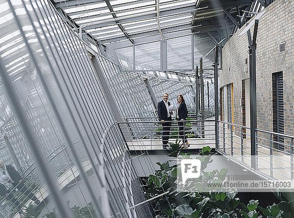 Geschäftsmann und Geschäftsfrau halten Globus in modernem Bürogebäude