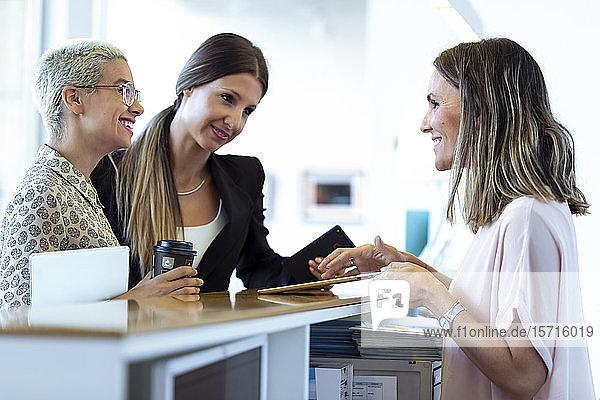 Zwei lächelnde Geschäftsfrauen im Gespräch mit Frau am Empfang