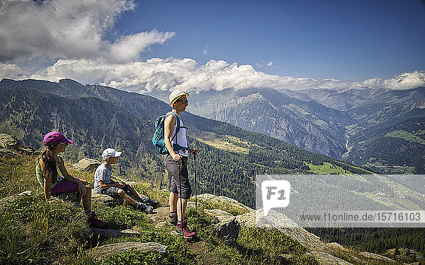 Mother with two children having a break from hiking in alpine scenery  Passeier Valley  South Tyrol  Italy