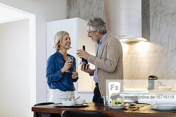 Mature couple having dinner in kitchen at home