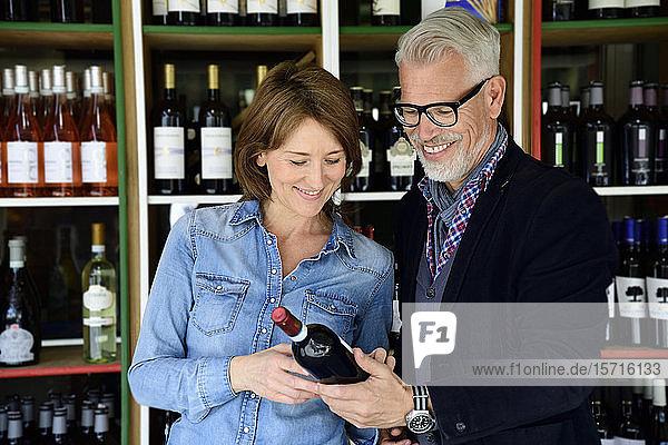 Reifes Paar wählt Flasche Wein in einer Weinhandlung