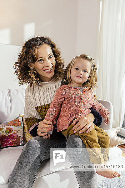 Portrait of happy mother with little daughter on couch at home