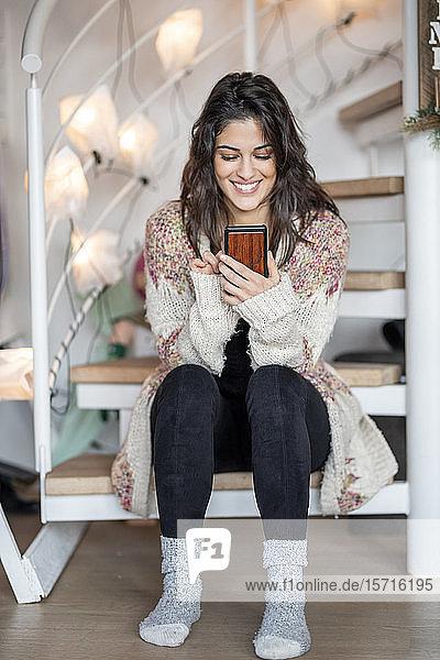 Porträt einer glücklichen jungen Frau  die zu Hause auf einer Treppe sitzt und ein Smartphone benutzt