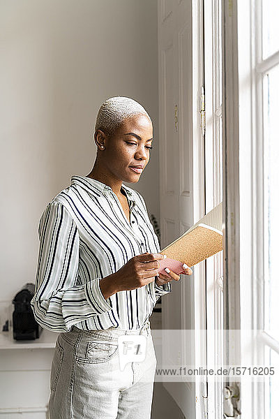 Woman reading notebook at the window