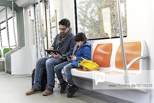 Vater und Tochter in der U-Bahn und mit Tablet und Smartphone