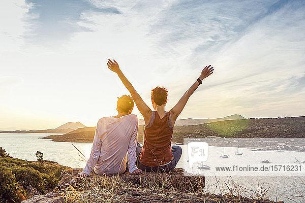 Ein Paar beobachtet den Sonnenuntergang am Kap Sounion  Attika  Griechenland