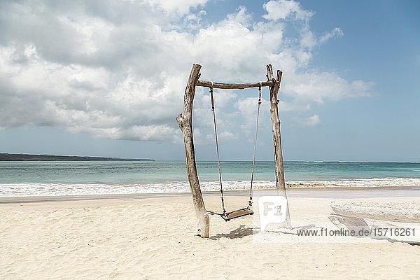 Indonesien  Bali  Jimbaran  Einfache Holzschaukel am Sandstrand