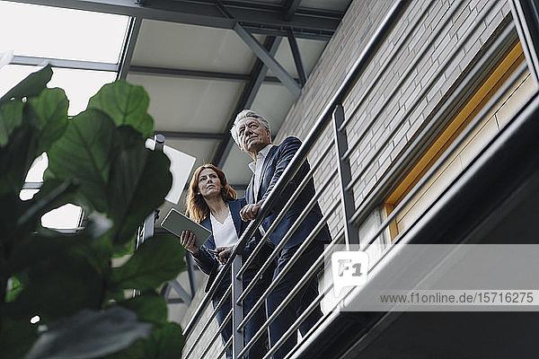 Geschäftsmann und Geschäftsfrau mit Tablett stehend in modernem Bürogebäude
