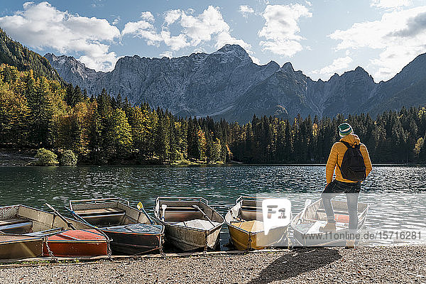 Hiker standing at mooring area with boats at Laghi di Fusine  Friuli Venezia Giulia  Italy