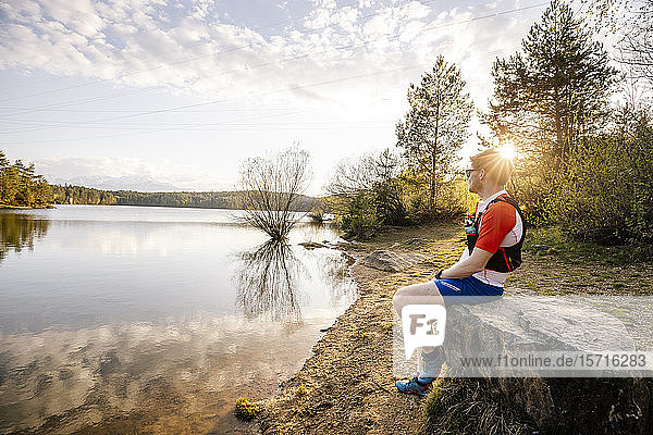 Sportive man sitting on a rock at the lakeside at sunset  Forstsee  Carinthia  Austria