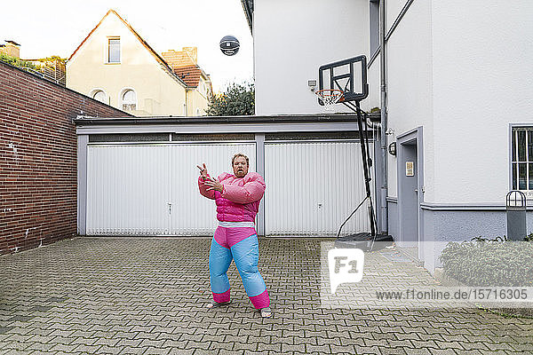 Portrait of a man with basketball wearing pink bodybuilder costume