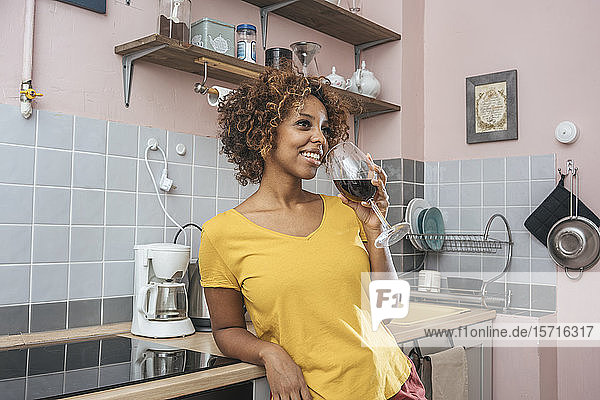 Smiling young woman drinking glass of red wine in kitchen