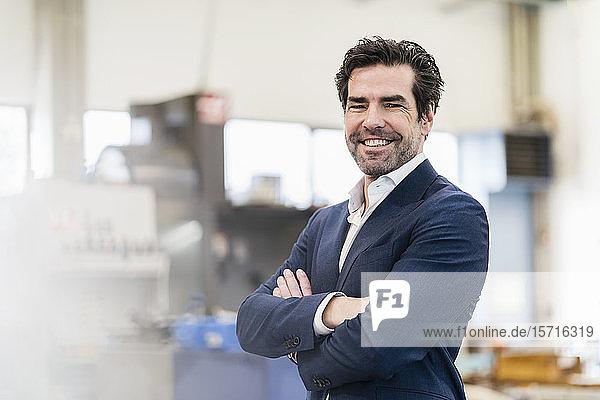 Porträt eines glücklichen Geschäftsmannes in einer Fabrik