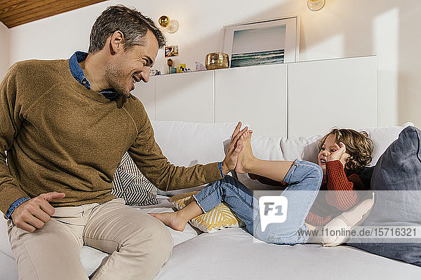 Father playfighting with daughter on couch