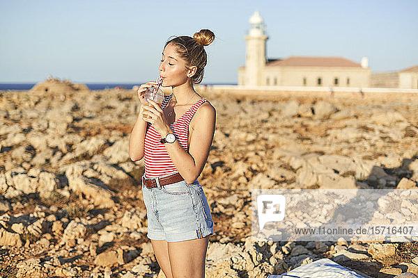Junge Frau trinkt Saft am felsigen Strand  Menorca  Spanien