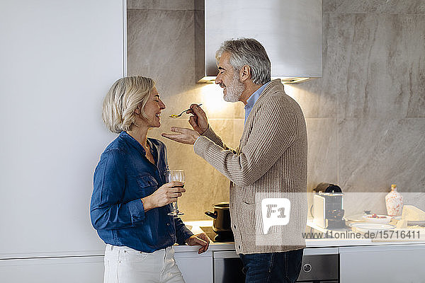 Happy mature couple preparing dinner in kitchen at home