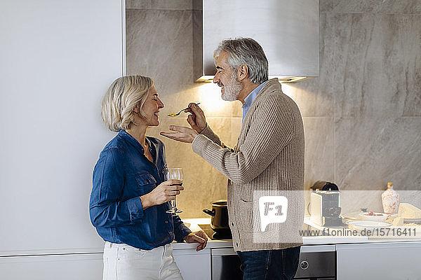 Glückliches reifes Paar bereitet das Abendessen in der heimischen Küche zu