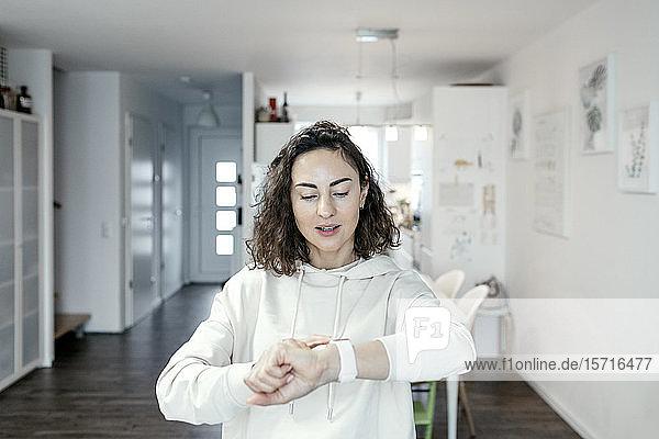Porträt einer Frau  die zu Hause auf ihre Smartwatch schaut