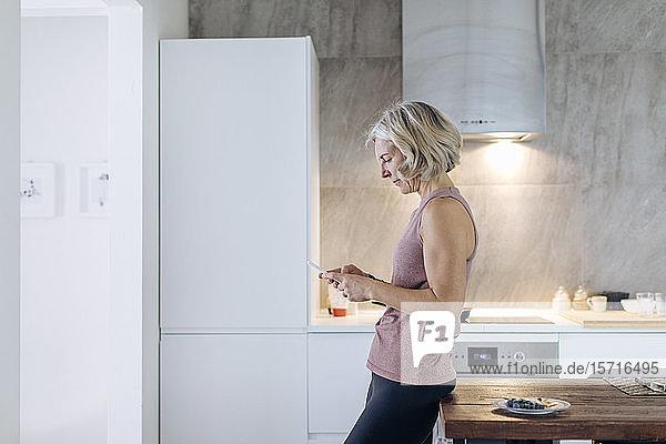 Reife Frau benutzt Mobiltelefon in der Küche zu Hause