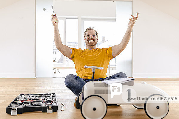 Happy man assembling toy car
