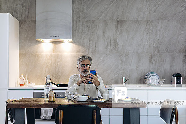 Mature man sitting at table in kitchen at home using cell phone