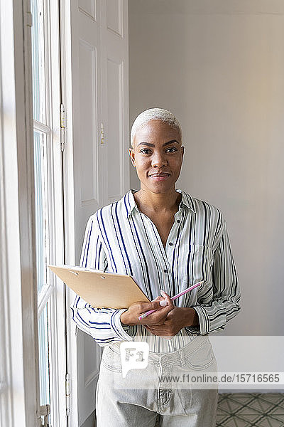 Portrait of smiling woman with clipboard and pencil at the window