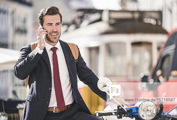 Junger Geschäftsmann mit Motorroller beim Telefonieren in der Stadt  Lissabon  Portugal