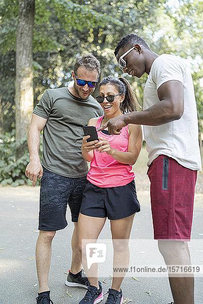 Freunde  die eine Pause vom Sport machen und sich ein Smartphone anschauen