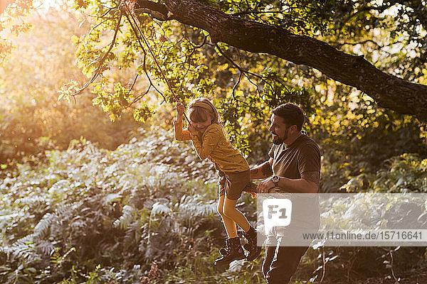 Kleines Mädchen schwingt sich mit Hilfe ihres Vaters auf einer Seilschaukel