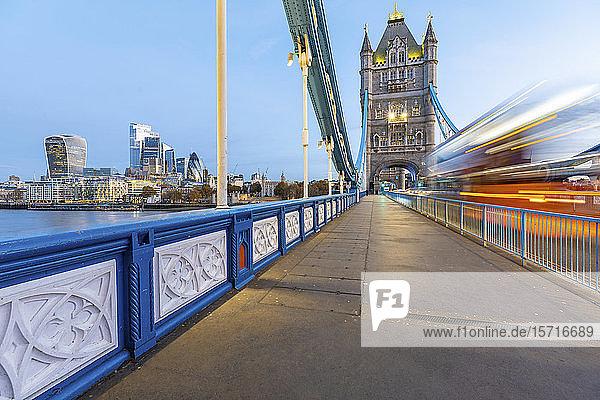 Großbritannien  England  London  verschwommene Bewegung eines Doppeldeckerbusses  der im Morgengrauen über die Tower Bridge fährt