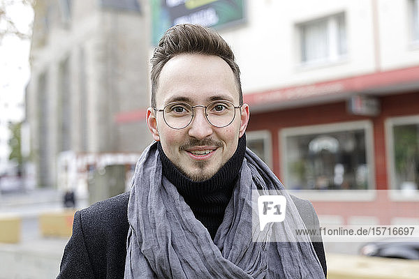 Portrait of smiling young man in the city in winter
