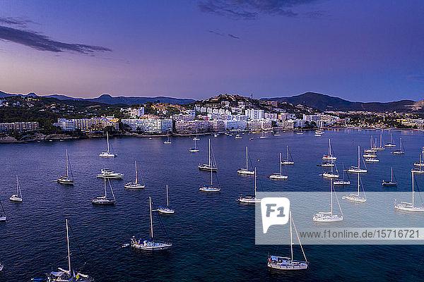 Spanien,  Mallorca,  Santa Ponsa,  In der Abenddämmerung im Küstengewässer schwimmende Boote mit der Stadt im Hintergrund