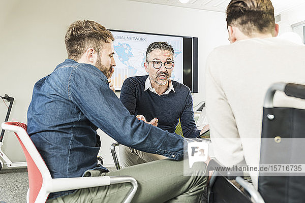 Three businessmen having a meeting in office