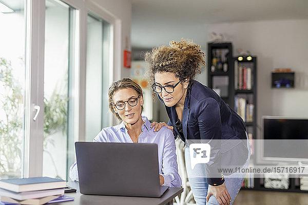 Zwei Businessfrauen mit Laptop auf dem Tisch zu Hause