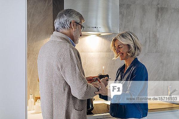 Älteres Paar feiert Geburtstag mit Kuchen in der heimischen Küche