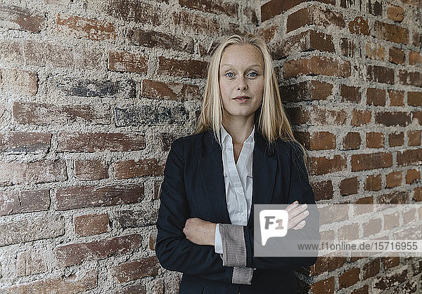 Porträt einer selbstbewussten jungen Geschäftsfrau an einer Ziegelmauer