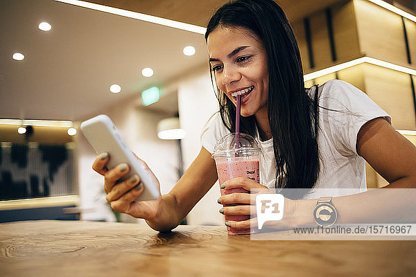 Black-haired woman drinking a smoothie and using smartphone in cafe