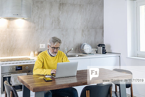 Mature man using laptop at table in kitchen at home