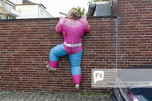 Man wearing pink bodybuilder costume climbing over a wall