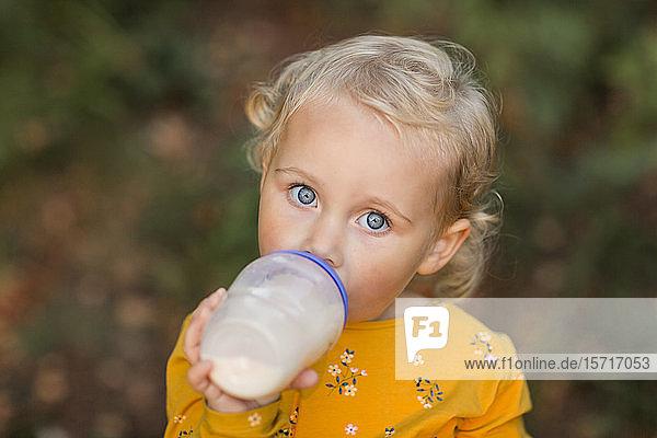 Porträt eines blonden Kleinkindes mit blauen Augen  das Milch aus einer Flasche trinkt