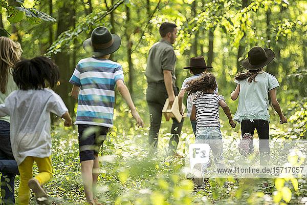 Schulkinder  die mit ihrem Lehrer im Wald spazieren gehen