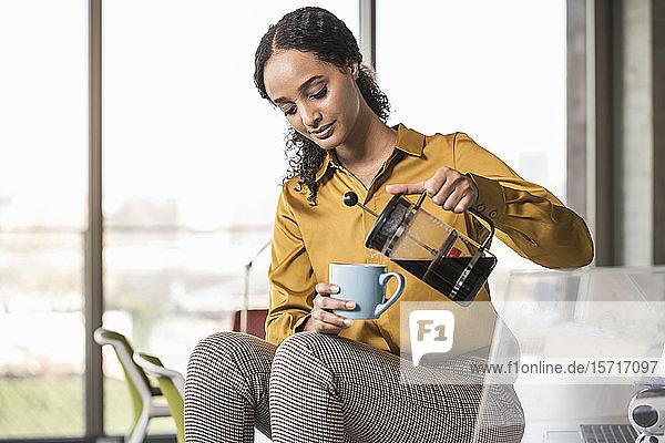 Young businesswoman sitting on desk in office having a coffee break