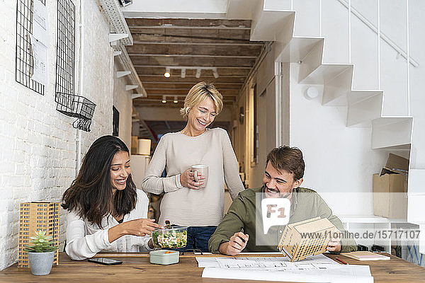 Three colleagues at desk in architect's office