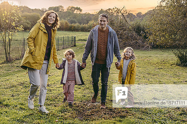 Portrait of happy family with two daughters walking on a meadow in autumn