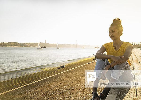 Junge Frau sitzt am Wasser und genießt die Aussicht bei Sonnenuntergang  Lissabon  Portugal
