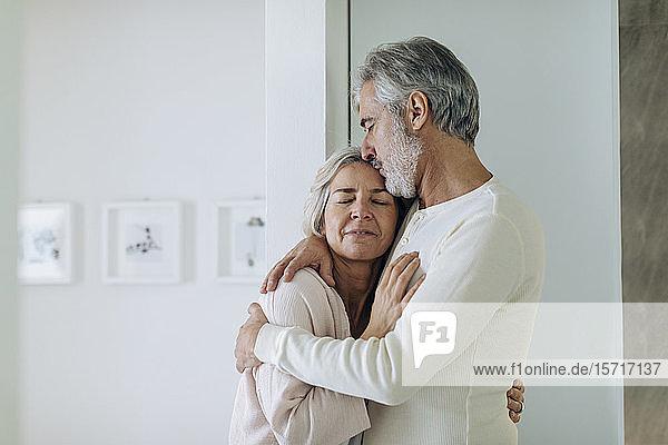Zärtliches  reifes Paar  das sich zu Hause umarmt Zärtliches, reifes Paar, das sich zu Hause umarmt