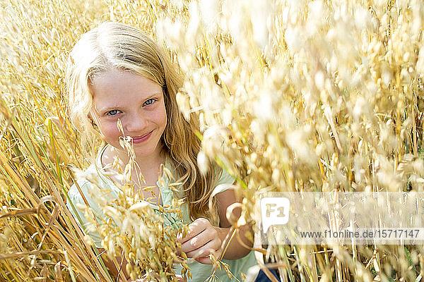 Lächelndes Mädchen steht im reifen Weizenfeld