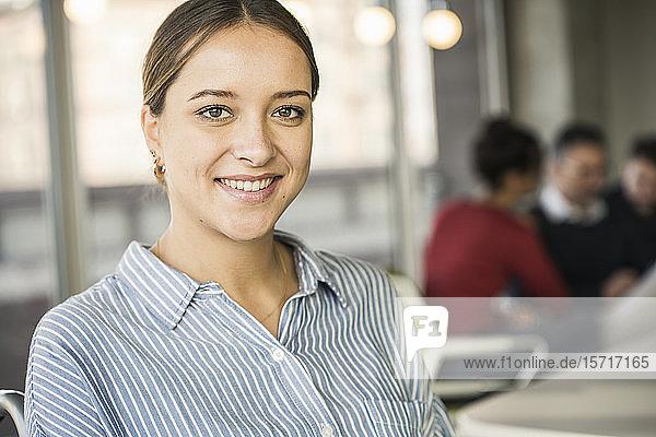 Porträt einer lächelnden jungen Geschäftsfrau während einer Besprechung im Amt